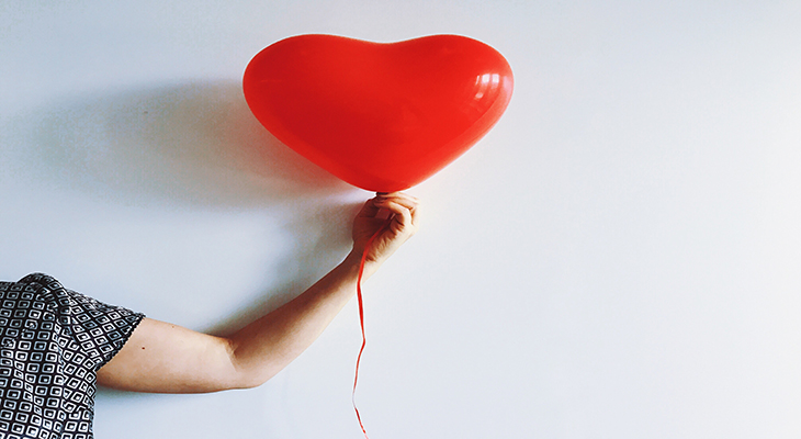 arm holding out a red balloon title=