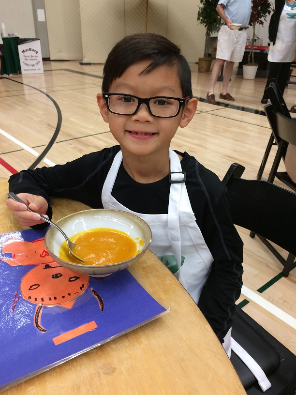 Young and older come together to raise funds to provide healthy food to those facing hunger in Santa Barbara County. A 9-year-old boy in glasses enjoys butternut squash soup at last year's Empty Bowls lunch