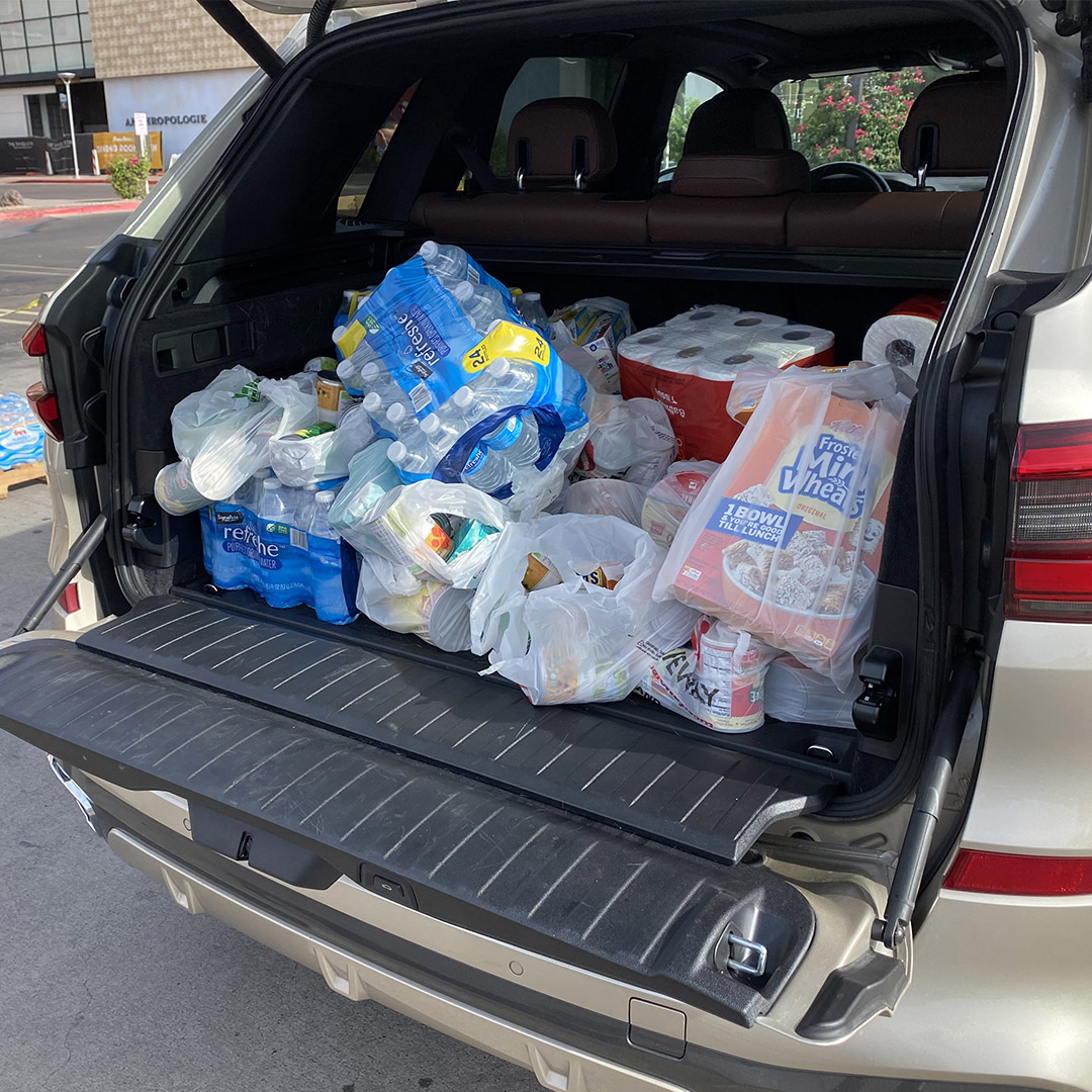 Auto with trunk open with bags of food to donate title=