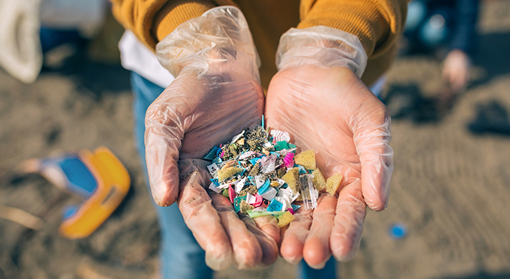 Photo of hands holding microplastics (small plastic pieces), with beach in the background. title=