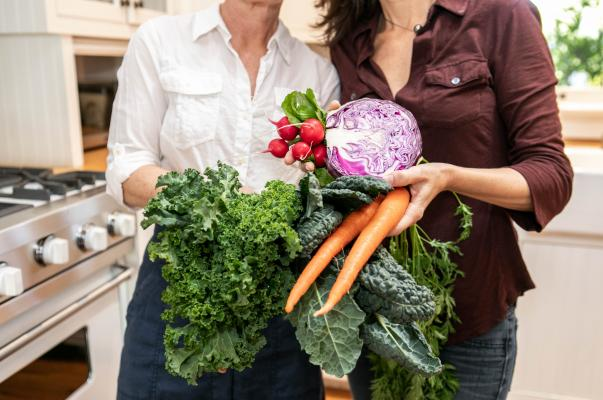 Two nutritionists hold a bunch of fresh vegetables, mostly crucifers, in support of the Foodbank of Santa Barbara County's Food as Medicine event on October 21. Cruciferous veggies pictures include purple cabbage, kale, swiss chard, radishes. Carrots are also pictured.