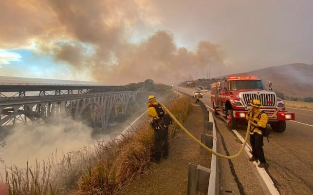 Firefighters extinguish flames Tuesday afternoon that have spotted ahead of the fire front along Highway 101 southbound at Vista Point, north of Refugio State Beach.  Fire activity near a ranch off Highway 101. (Photo: Mike Eliason / SBCFD)