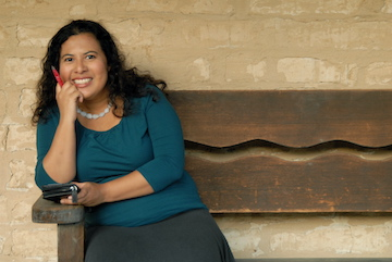 Poet Melinda Palacio seated on a bench with pen in hand. title=