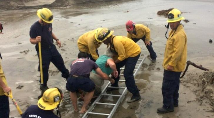 Firefighters Rescue Woman Trapped in Sand title=