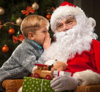 little boy whispering into Santa's ear