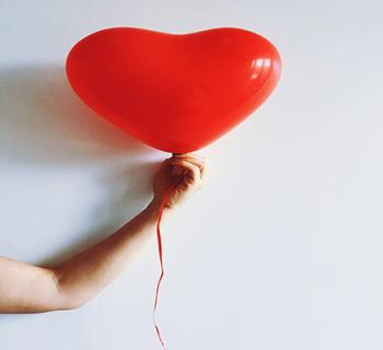 arm holding out a red balloon